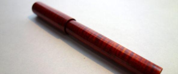 「インク染・拭き漆」仕上げのメープル軸万年筆 (スティロアート)。波打つ縮杢が艶やかに際立つ